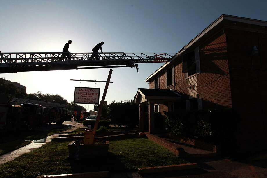 Firefighters approach the roof of the Park Place Efficiency Apartments after smoke forced some residents to jump from second-story windows. Photo: Johnny Hanson / © 2012  Houston Chronicle