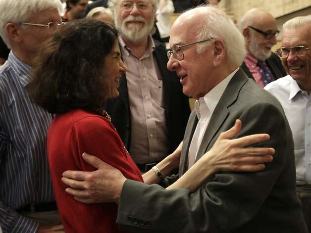 "British physicist Peter Higgs, right, congratulates Fabiola Gianotti, ATLAS experiment spokesperson, after her results presentation during a scientific seminar to deliver the latest update in the search for the Higgs boson at the European Organization for Nuclear Research (CERN) in Meyrin near Geneva, Switzerland, Wednesday, July 4, 2012. The head of the world's biggest atom smasher is claiming discovery of a new particle that he says is consistent with the long-sought Higgs boson known popularly as the ""God particle"" which is believed to give all matter in the universe size and shape. (AP Photo/Denis Balibouse, Pool) Photo: Denis Balibouse, Associated Press"