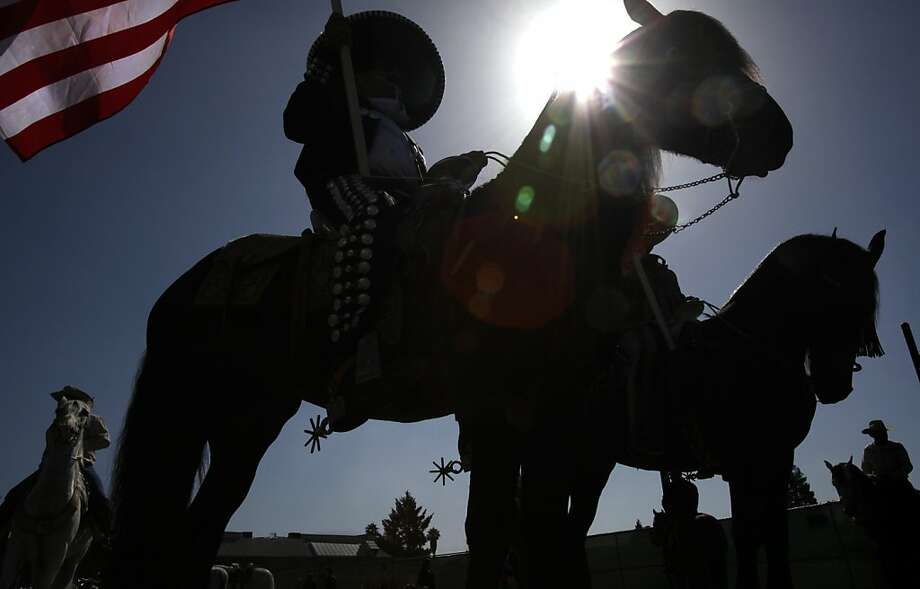 Jose Pelayo holds the American flag as he and other members of the Agaveros show horse equestrian group line up at the Fourth of July parade in Alameda, Calif., Wednesday, July 4, 2012. Photo: Sarah Rice, Special To The Chronicle