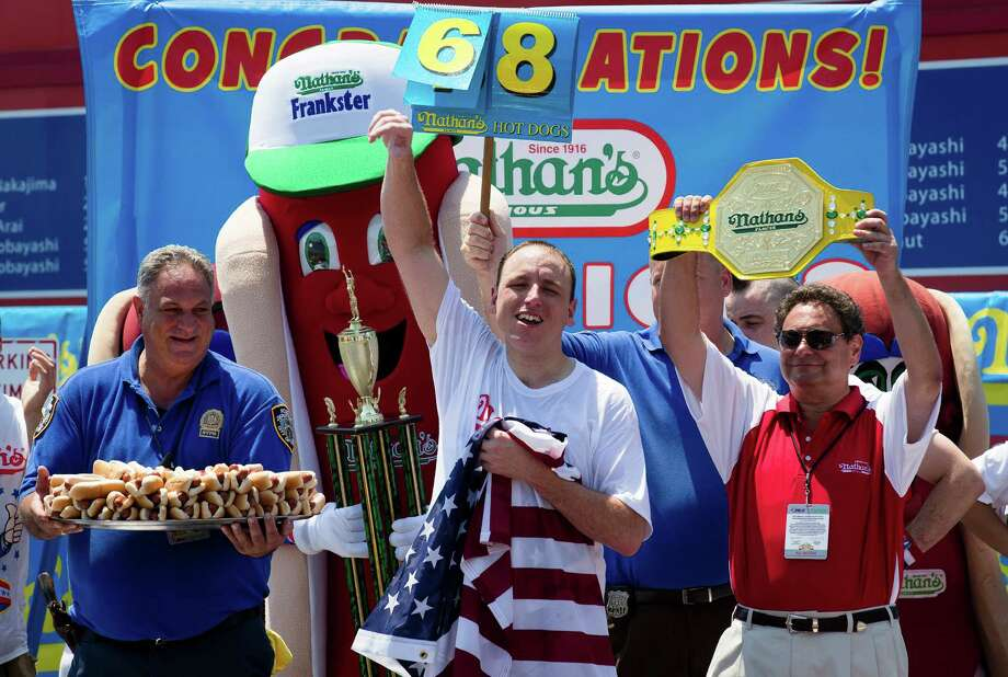 Five-time reigning champion Joey Chestnut celebrates after he wins his sixth straight Coney Island hot dog eating contest on Wednesday, July 4, 2012  at Coney Island, in the Brooklyn borough of New York. Chestnut tied his personal best and the record with eating 68 hot dogs. Last year, Chestnut won with 62 hot dogs. (AP Photo/John Minchillo) Photo: John Minchillo