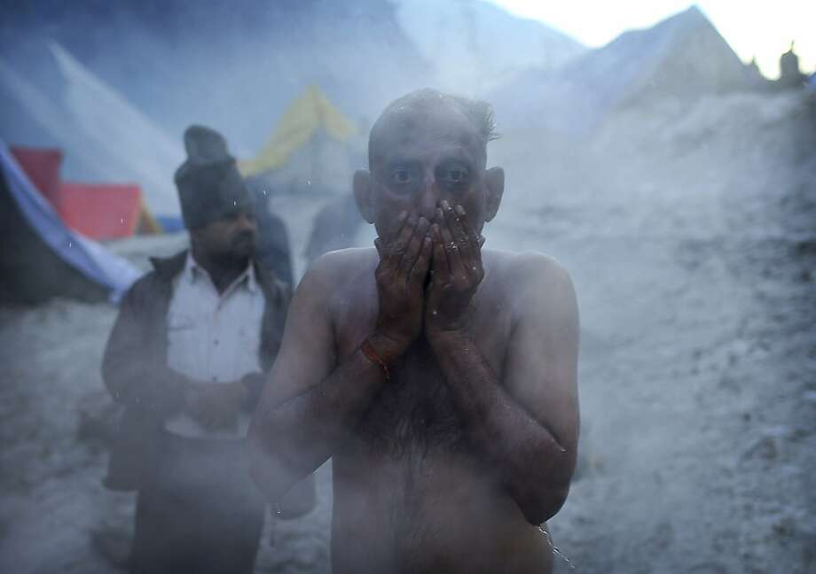 In this picture taken Friday, June 29, 2012, steam comes off the body of an Indian Hindu pilgrim after bathing on a cold morning during the traditional journey to the Amarnath cave, at Sangam, 135 kilometers (83 miles)  from Srinagar, India. Thousands of pilgrims annually go to the remote Himalayan shrine of Amarnath at 3,888 meters (12,756 feet) above sea level to worship an icy stalagmite representing Shiva, the Hindu god of destruction. (AP Photo/Kevin Frayer) Photo: Kevin Frayer, Associated Press