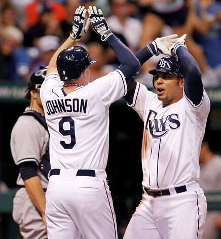 Tampa Bay Rays' Carlos Pena, right, is congratulated by Elliot Johnson after his two-run home run scored both during the seventh inning of a baseball game against the New York Yankees, Wednesday, July 4, 2012, in St. Petersburg, Fla. (AP Photo/Mike Carlson) Photo: Mike Carlson