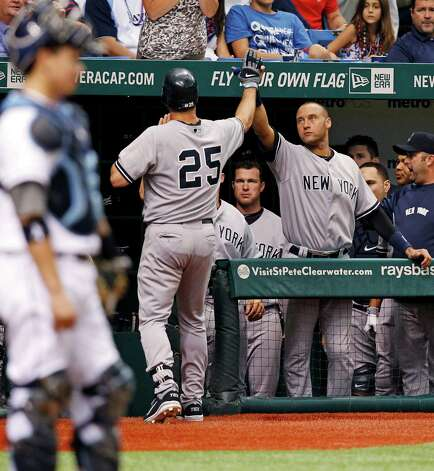 New York Yankees' Mark Teixeira (25) is congratulated by Derek Jeter after his home run during the seventh inning of a baseball game, Wednesday, July 4, 2012, in St. Petersburg, Fla. (AP Photo/Mike Carlson) Photo: Mike Carlson