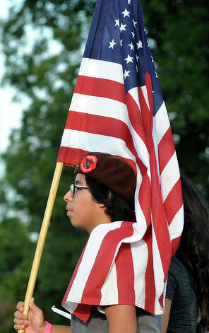 A member of the Brown Berets carries the flag during the second annual March for Immigrant Rights on Wednesday, July 4, 2012. Photo: Billy Calzada, San Antonio Express-News / © 2012 San Antonio Express-News