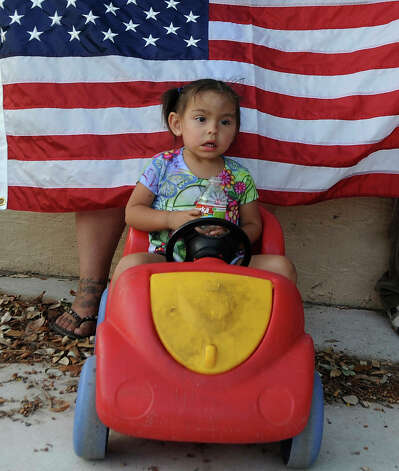 Xochitl Resendiz, 2, watches a rally after the second annual March for Immigrant Rights at Elmendorf Park on Wednesday, July 4, 2012. Participants prayed and sang the Star Spangled Banner. Photo: Billy Calzada, San Antonio Express-News / © 2012 San Antonio Express-News
