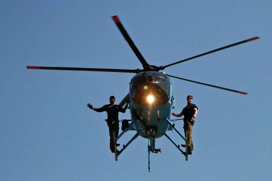 SWAT team members hitch a helicopter ride in May 2010 during a presentation for Houston-area students by HPD's Training Division. Photo: Michael Paulsen / Houston Chronicle