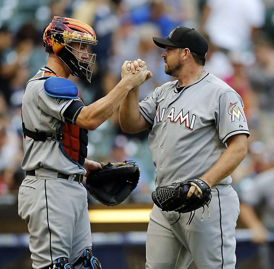 Miami Marlins John Buck, left, and Heath Bell meet after the Marlins defeated the Milwaukee Brewers 7-6 in a 10-inning baseball game on Wednesday, July 4, 2012, in Milwaukee. (AP Photo/Tom Lynn) Photo: Tom Lynn, Associated Press