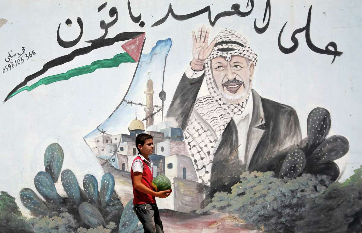 A Palestinian youth walks next to a mural depicting late Palestinian leader Yasser Arafat, in the northern West Bank village of Kabatyeh, Wednesday, July 4, 2012. Arabic text quotes a famous idiom meaning