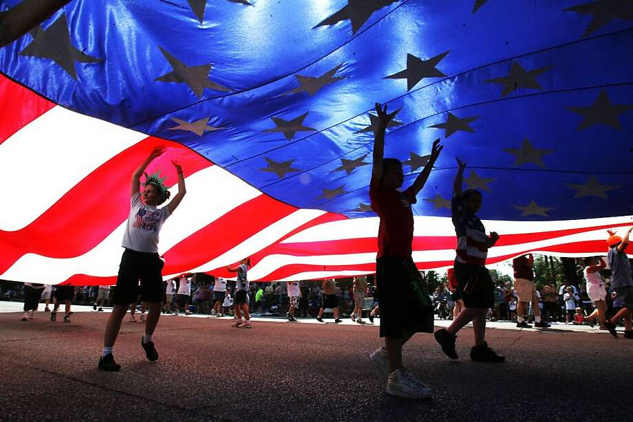 Young Tower members assist in carrying a large United States flag down the LaPorte Jaycees Fourth of July parade route in LaPorte, Ind., Wednesday, July 4, 2012. (AP Photo/The LaPorte Herald-Argus, Angus M. Thuermer Jr.) Photo: Bob Wellinski, Associated Press