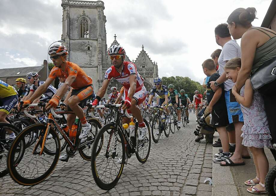 The pack leaves Abbeville during the start of the fourth stage of the Tour de France cycling race over 214.5 kilometers (133.3 miles) with start in Abbeville and finish in Rouen, France, Wednesday July 4, 2012. (AP Photo/Laurent Cipriani) Photo: Laurent Cipriani, Associated Press