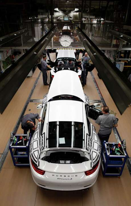 Employees work on a Porsche AG 911 Carrera S automobile as it travels along the production line inside the company's factory in Stuttgart, Germany, on Monday, Jan. 30, 2012. Porsche SE's worldwide deliveries rose 4.8 percent to 9,613 cars and sport-utility vehicles, led by a 30 percent jump for its Panamera model and a 15 percent gain for the 911, the company said in an e-mailed statement. Photographer: Simon Dawson/Bloomberg Photo: Simon Dawson / © 2012 Bloomberg Finance LP