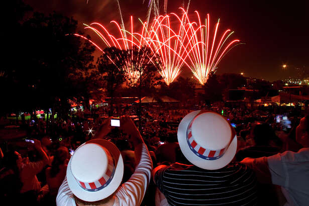 Maureen Krull, left, sits with her son, Bill Krull right, as they watch the fireworks show during the Freedom Over Texas event, Houston's Fourth of July celebration at Eleanor Tinsley Park Wednesday, July 4, 2012, in Houston.