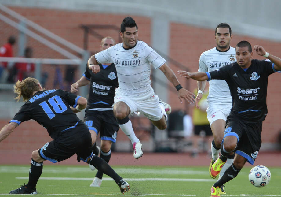 Scorpions forward Esteban Bayona (11) jumps over the Edmonton Eddies' Paul Hamilton (18) as he tries to make his way up field during the teams' match on Wednesday, July 4, 2012, at Heroes Stadium. Photo: John Albright, For The Express-News