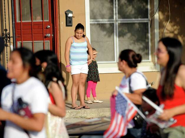 West San Antonio residents watch as the March for Immigrant Rights passes by along Brazos Street on Wednesday, July 4, 2012. Photo: Billy Calzada, San Antonio Express-News / © 2012 San Antonio Express-News