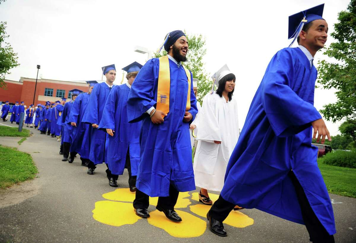 """Seymour High School graduates proceed down """"Wildcat Way"""" to the football field for the commencement ceremony Tuesday, June 19, 2012 at the school in Seymour, Conn."""