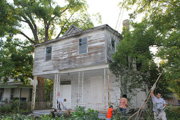 Volunteers from the Dignowity Hill Neighborhood Association clean up an abandoned house at 714. N. Pine St. on June 16.