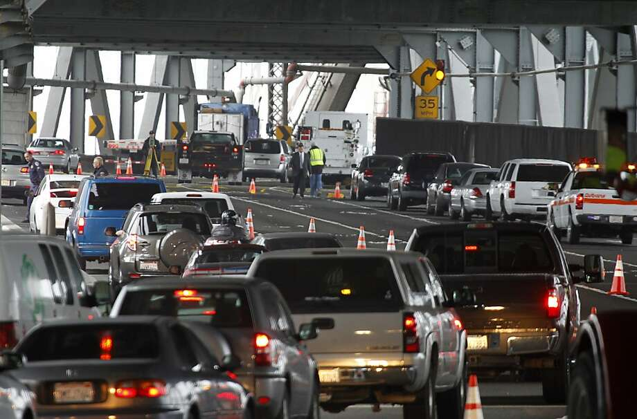 Investigators gather evidence after an overnight police pursuit ended in a shooting and crash just east of Yerba Buena Island on the lower deck of the Bay Bridge in San Francisco, Calif. on Thursday, July 5, 2012. The Highway Patrol closed off four-lanes of eastbound traffic for several hours snarling traffic heading for the East Bay. Photo: Paul Chinn, The Chronicle