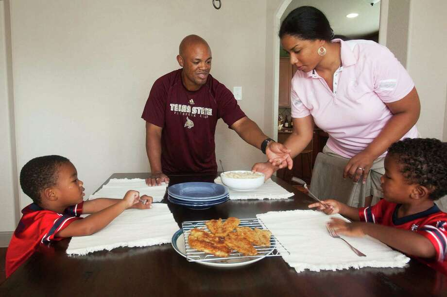 The Antoine family, Ronald, center, and his wife Zenarae prepare for dinner together with their 3-year-old twins, Zavier, left,  and Zachary right, at their home in Kyle, Texas.  Ronald Antoine and his wife Zenarae hold college coaching positions more than 1,600 miles apart. Ronald is an assistant football coach at Fresno State in California while Zenarae is the head women's basketball coach at Texas State in San Marcos. Their 3-year-old twin sons Zachary and Zavier live with Zenarae in Kyle, Texas, Wednesday, June 27, 2012.  Valentino Mauricio/The Enterprise Photo: Valentino Mauricio
