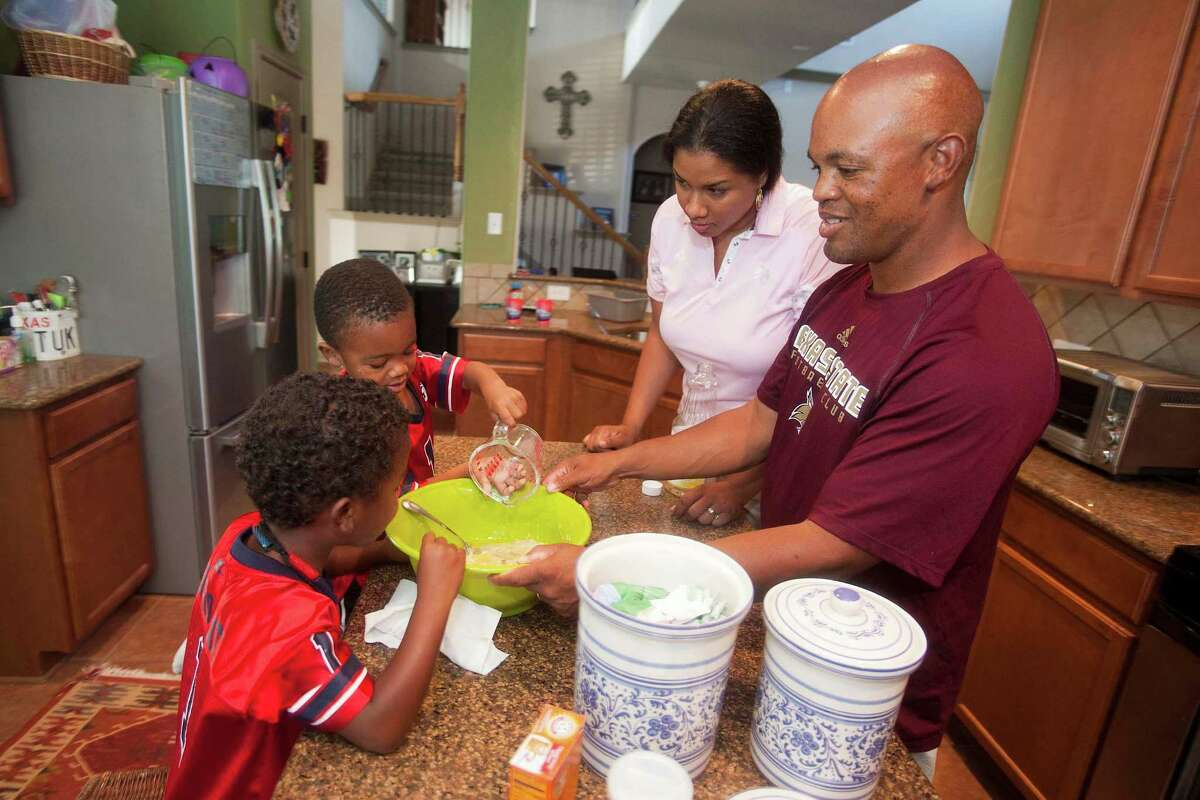 The Antoine twins, 3-year-old Zachary, left, and Zavier, gathers in the kitchen with their mom Zenarae, center, and their dad Ronald for a baking project at their home in Kyle, Texas. Ronald Antoine and his wife Zenarae hold college coaching positions more than 1,600 miles apart. Ronald is an assistant football coach at Fresno State in California while Zenarae is the head women's basketball coach at Texas State in San Marcos. Wednesday, June 27, 2012. Valentino Mauricio/The Enterprise
