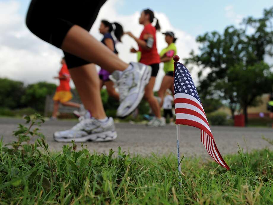 Runners pass by a small flag placed along Lemonwood Avenue at the start of the Fiesta Castle Hills Independence Day Firecracker 5K Run/Walk on Wednesday. Photo: John Albright / For North Centra