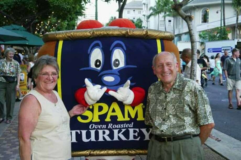 HONOLULU, HI - APRIL 5:  Tourists pose with SPAMMY the mascot during the Waikiki SPAM JAM Festival. The Waikiki SPAM JAM is a celbration of one of Hawaii's favorite foods, the mystery meat SPAM. The three day even concluded on Saturday with live performers, food boths, and a SPAM eating contest. (Phil Mislinski / Getty Images) (Getty Images)