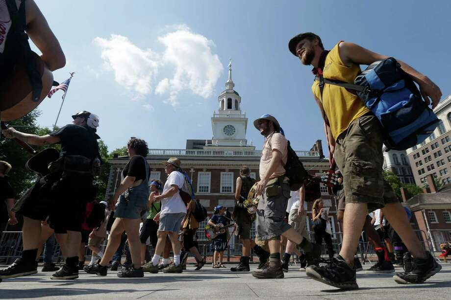 Members of the Occupy Wall Street movement march past Independence Hall, Thursday, July 5, 2012, in Philadelphia. Occupy groups from across the country gathered this past week in Philadelphia for a national gathering seeking to unify their far-flung movement against economic inequality and now are marching to New York. (AP Photo/Matt Rourke) Photo: Matt Rourke, Associated Press / AP