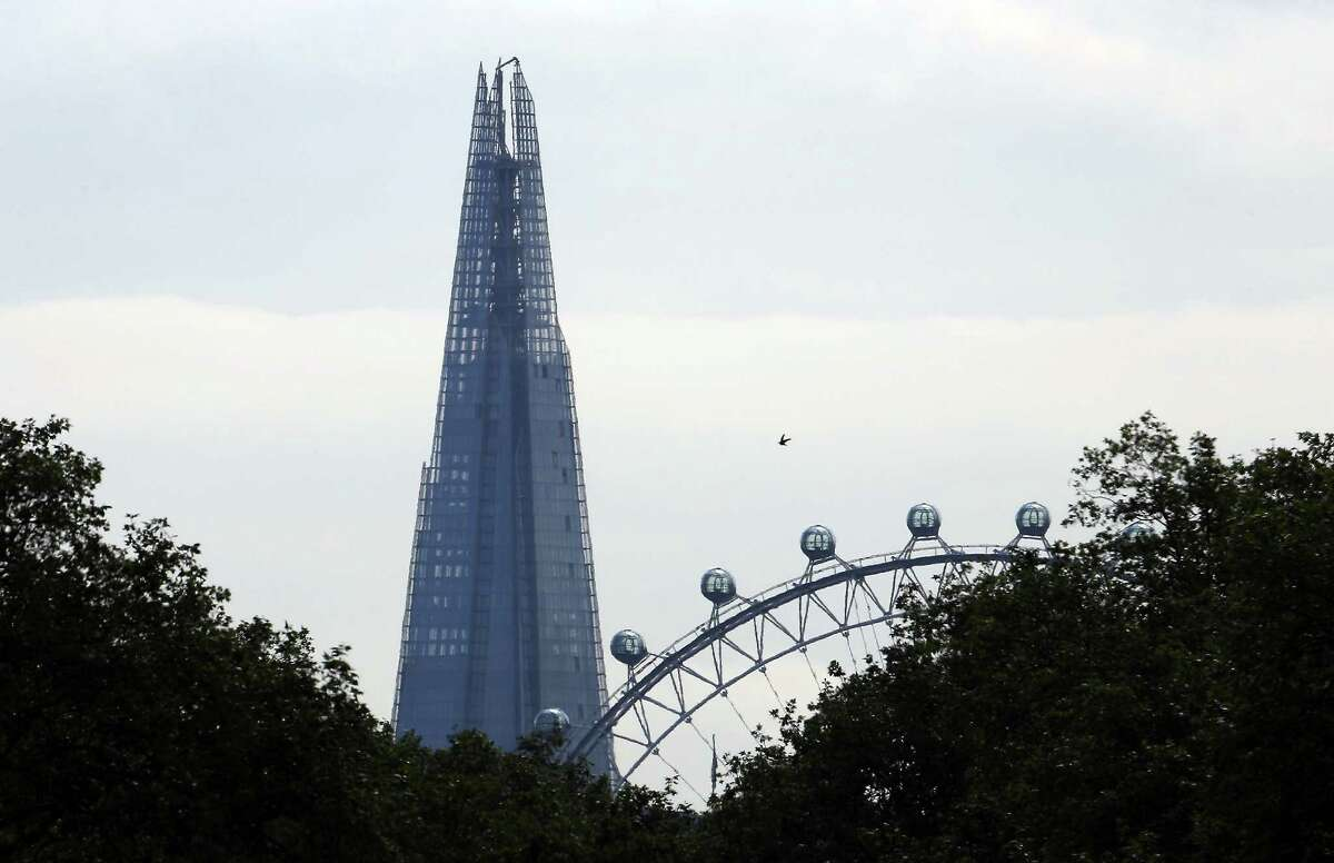 The Shard rises above The London Eye Ferris wheel seen from Hyde Park on Thursday in London, England. The European Union's highest building is to be formally inaugurated with a laser show which will also be streamed live on the internet. (Photo by Peter Macdiarmid/Getty Images)