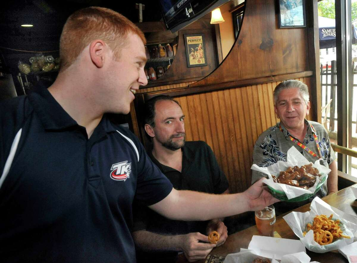 Ryan Dempsey serves Buffalo Hot and Ugly Elf birthday wings to Lev Aks, of Golden's Bridge, N.Y., and Lew Horowitz, of Fairfield, right, at TK's American Cafe in Danbury Thursday, July 5, 2012. It is Horowitz's birthday.