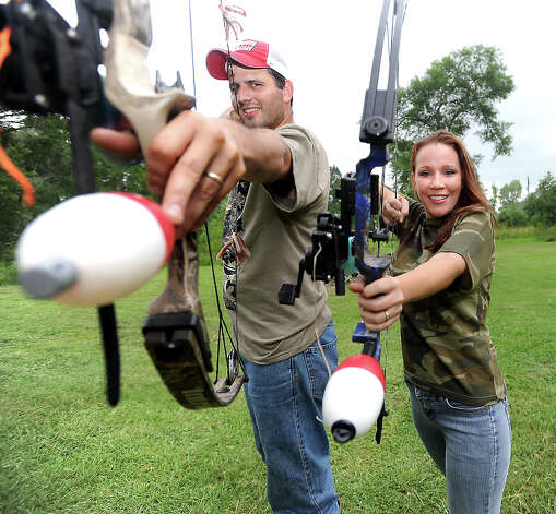 Jared Franks and September Franks pose with their bows at their home in Silsbee, Tuesday, June 19, 2012. The Franks bowfish for gar and carp. Tammy McKinley/The Enterprise Photo: TAMMY MCKINLEY