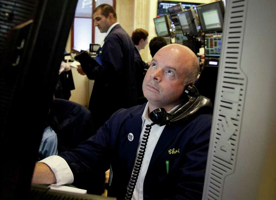 FILE - In this July 3, 2012 file photo, a trader studies his screen as he works on the floor of the New York Stock Exchange. U.S. stock futures fluctuated in volatile trading Thursday, July 5, 2012, as banks in China and Europe took action to bolster flagging economies and poor retail sales for June offset some promising job numbers from the Labor Department. (AP Photo/Richard Drew, File) Photo: Richard Drew / Copyright 2012 The Associated Press. All rights reserved. This material may not be published, broadcast, rewritten or redistribu