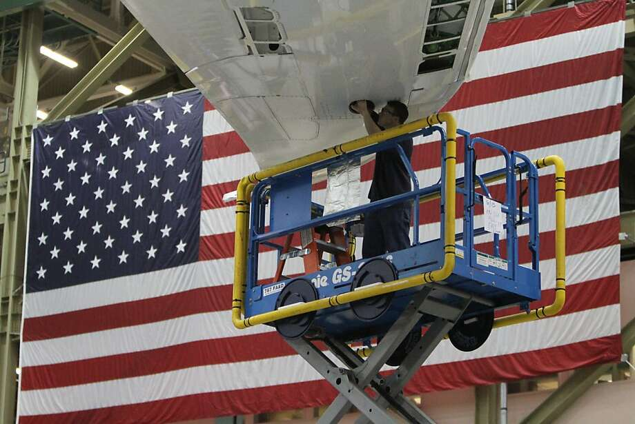 In this June 13, 2012 photo, a worker on Boeing's 787 assembly line works under a wing with a U.S. flag in the background, in Everett, Wash. A spokesperson for Boeing said the company will be showcasing a full range of innovative new products, systems and services at The Farnborough International Airshow 2012. The show will take place in Farnborough, U.K., starting on July 9, 2012. (AP Photo/The Seattle Times, Ken Lambert) Photo: Ken Lambert, Associated Press