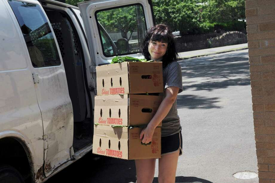 Stacia Porsser, 24, of Stone Gardens Farm in Shelton, brings boxes of vegetables to St. Paul Lutheran Church in Byram, Thursday, July 5, 2012. The farm recently expanded its community supported agriculture program with a new pick-up location at the church. The farm's CSA program allows customers to make an annual payment at the beginning of the growing season directly to the farm, which will entitle them to a box of fresh vegetables each week during the growing season, from the beginning of June to the end of October. Photo: Helen Neafsey / Greenwich Time