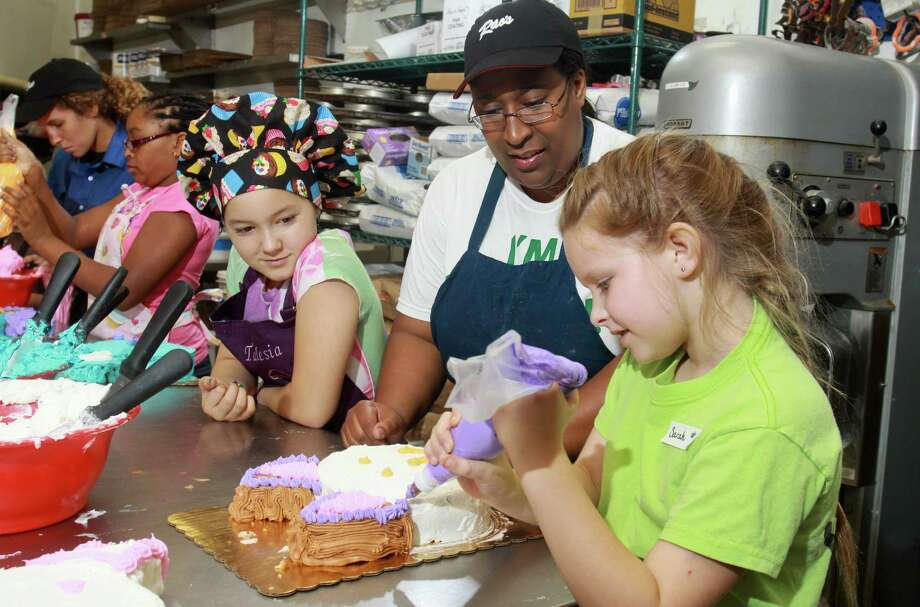 Talesia Byrd, from left, pays attention as chef Octavia Williams watches Sarah Brawn decorate her cake at the Rao's Bakery & Coffee Cafe summer Bake Camp. Photo: Gary Fountain / Copyright 2012 Gary Fountain.