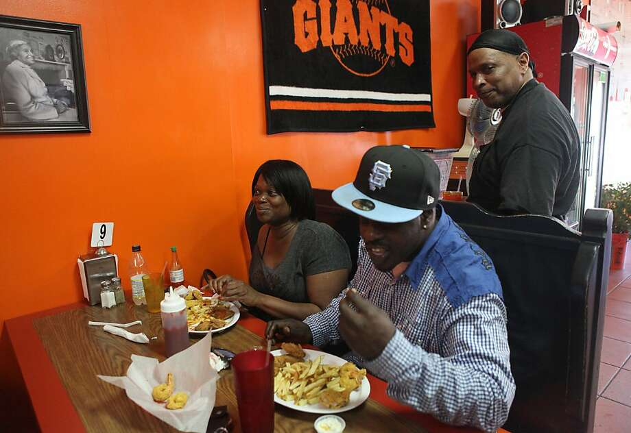 Chef Geeto Banks (standing right) checking on his niece Danita Blankenship (left) and her husband Johnny Blankenship (right) as they have prawns and wings at Frisco Fried in San Francisco, Calif.,  on Saturday, June 30, 2012. Photo: Liz Hafalia, The Chronicle