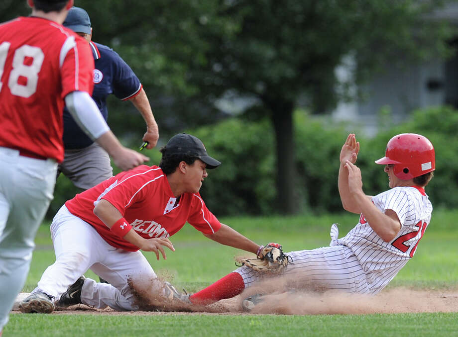 Redmen third baseman Matt Roskoff tags-out Tyler Imbo of BANC during the top of the first inning of Senior Babe Ruth baseball game between BANC and Redmen at Havemeyer Field in Greenwich, Thursday, July 5, 2012. Imbo was trying to stretch a double into a triple but was thrown out. Photo: Bob Luckey / Greenwich Time