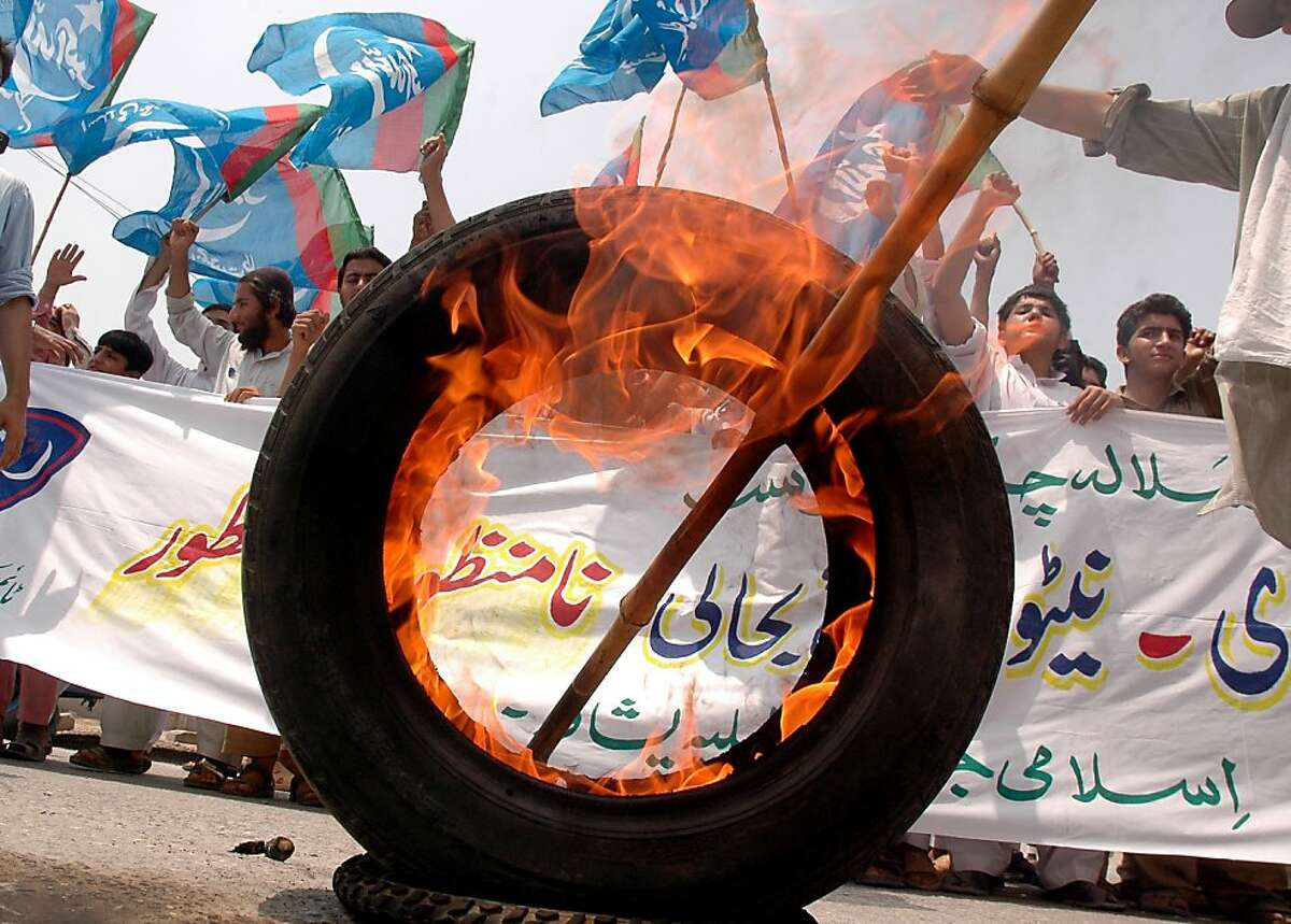 """Activists of Pakistani political and Islamic party Jammat-e-Islami (JI) shout slogans during a protest in Peshawar on July 5, 2012, against the Pakistani government's open NATO supplies route to Afghanistan. The first trucks supplying NATO troops in Afghanistan crossed the border from Pakistan on July 5, after Islamabad ended a seven-month blockade. Pakistan closed overland routes for NATO convoys into its war-torn neighbour after a botched US air raid in November killed 24 Pakistani soldiers at a border post, plunging ties between the """"war on terror"""" allies to a new low. AFP PHOTO / HASHAM AHMEDHASHAM AHMED/AFP/GettyImages"""
