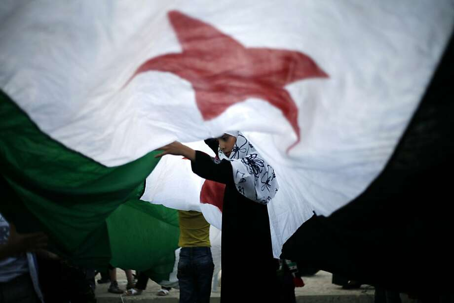 A Syrian girl lifts the center of a giant revolutionary flag during a protest against Bashar Assad, in front the Syrian embassy in Amman, Jordan, Thursday, July 5, 2012.  (AP photo/Mohammad Hannon) Photo: Mohammad Hannon, Associated Press