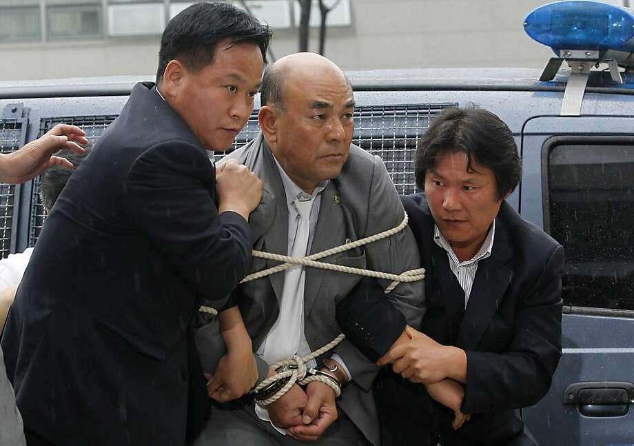 Left-wing South Korean activist Ro Su-Hui is led away tied up and cuffed by security officials into a police station in the border city of Paju on July 5, 2012. A left-wing South Korean activist was detained when he returned home from an illegal trip to North Korea and a meeting with its ceremonial head of state, police said.     REPUBLIC OF KOREA OUT  AFP PHOTO / DONG-A ILBODONG-A ILBO/AFP/GettyImages Photo: Dong-a Ilbo, AFP/Getty Images