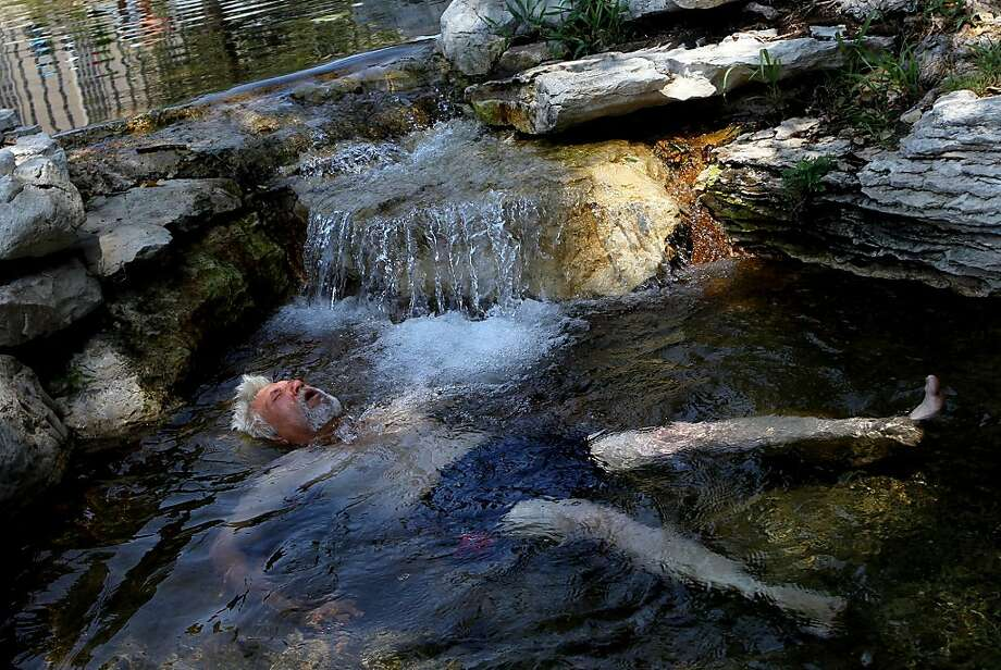 """Peter Ely, of St. Louis, cools off in a lagoon Thursday, July 5, 2012, at Forest Park in St. Louis. """"I've come here a couple of times this summer. I didn't think I was going to make it over here. It was so drained from walking,"""" said Ely. (AP Photo/St. Louis Post-Dispatch, Laurie Skrivan)  EDWARDSVILLE INTELLIGENCER OUT; THE ALTON TELEGRAPH OUT Photo: Laurie Skrivan, Associated Press"""