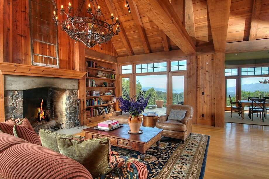 The great room, made from post and beam construction, has a cathedral ceiling, a chandelier, walls of built-in bookshelves and a huge stone and brick fireplace. Photo: Matt McCourtney