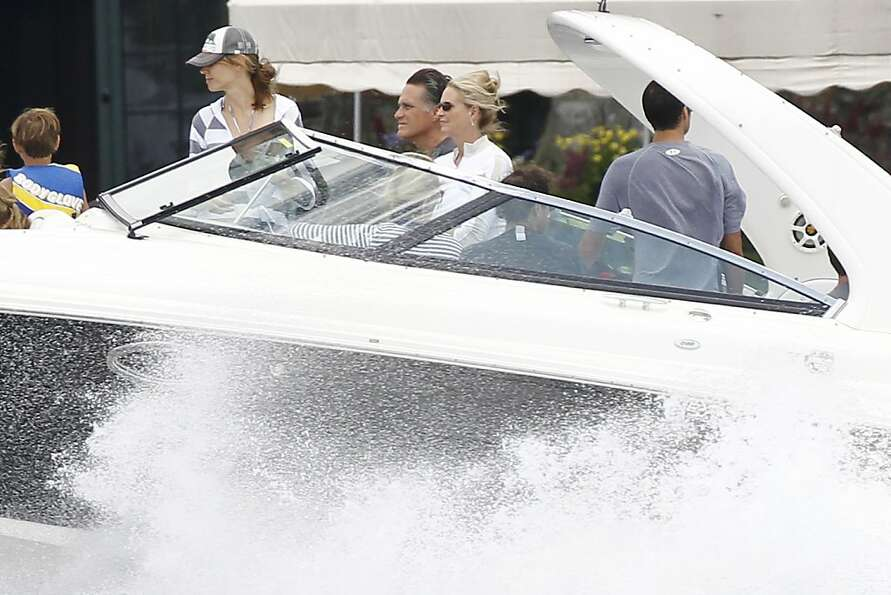 Republican presidential candidate Mitt Romney drives his boat with his famiy on Lake Winnipesaukee i