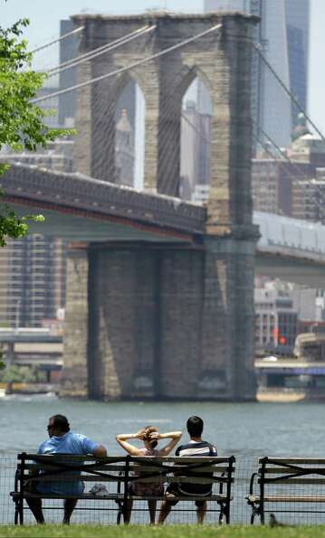 People rest on a bench at Brooklyn Bridge Park which features a close-up view of the Brooklyn Bridge