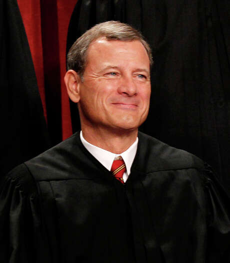 """FILE - In this Oct. 8, 2010 file photo, Chief Justice John Roberts is seen during the group portrait at the Supreme Court Building in Washington. Breaking with the court's other conservative justices, Roberts announced the judgment that allows the law to go forward with its aim of covering more than 30 million uninsured Americans. Roberts explained at length the court's view of the mandate as a valid exercise of Congress' authority to """"lay and collect taxes."""" The administration estimates that roughly 4 million people will pay the penalty rather than buy insurance.  (AP Photo/Pablo Martinez Monsivais, File) Photo: Pablo Martinez Monsivais / AP"""
