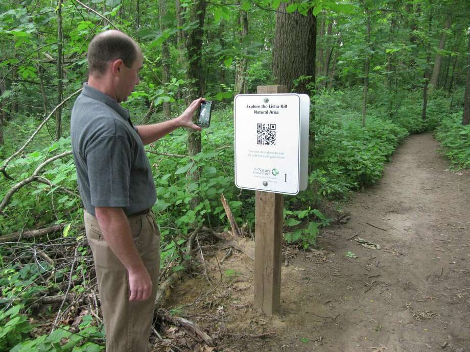 Photo by Gillian Scott Troy Weldy, director of ecological management for the New York Chapter of the Nature Conservancy, uses his smartphone to scan a new audio guide QR code at the Lisha Kill Natural Area in Niskayuna.