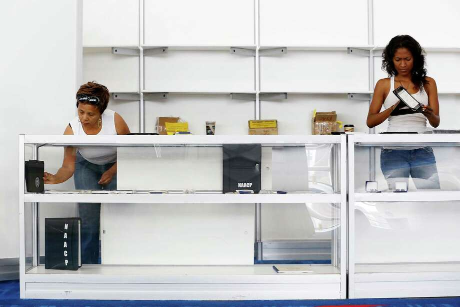 Nancy Bailey, left, and Tehra Williams of Baltimore, set up a boutique two days before the NAACP annual conference at the George R. Brown Convention Center in Houston. Photo: TODD SPOTH / © TODD SPOTH, 2012