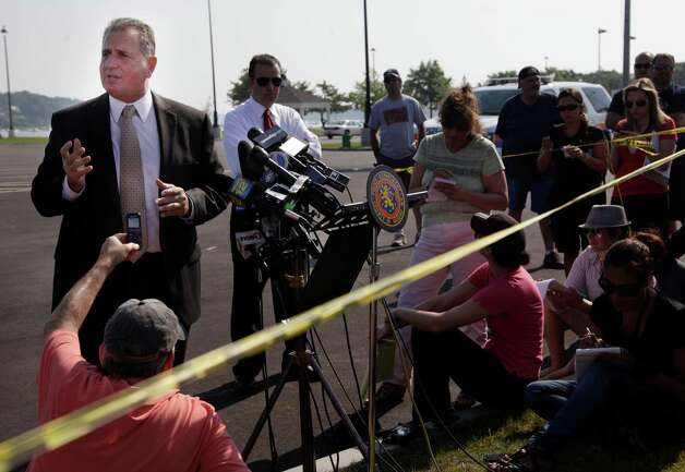 Nassau County Police Department Det. Lt. John Azzata, left, gives information about a fatal boating accident during a news conference in Oyster Bay, N.Y., Thursday, July 5, 2012.  Police say three bodies pulled out of New York's Long Island Sound after a yacht capsized on the Fourth of July were all children. The bodies of the 12-year-old boy and two girls, ages 11 and 8, were recovered from the boat's cabin. Twenty-four other people were rescued, and were treated and released. (AP Photo/Seth Wenig) Photo: Seth Wenig