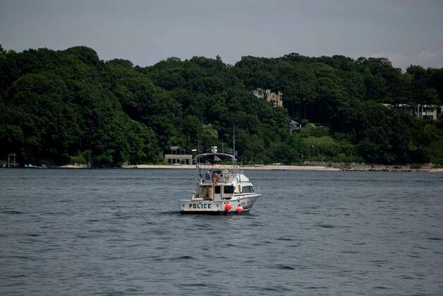 A Nassau County Police boat at the opening to Oyster Bay where a boat capsized and sank, at Theodore Roosevelt Memorial Park, in Oyster Bay, N.Y., July 5, 2012. Three children were found dead inside the cabin of the boat on Wednesday night, as it returned from a fireworks show celebrating the Fourth of July, the Nassau County police said Thursday morning. (Michael Kirby Smith/The New York Times) Photo: MICHAEL KIRBY SMITH / NYTNS