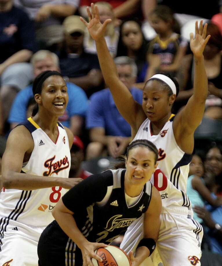 Indian Fever's Briann January, right, stops San Antonio Silver Stars' Becky Hammon, center, from passing the ball during the first half of an WNBA basketball game, Thursday, July 5, 2012, in Indianapolis. Photo: AP Photo / The Indianapolis Star,  Kenneth L. Hawkins Jr.