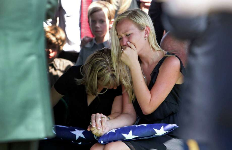 Kim Tisdale left, the wife of Lt. Col. Roy Tisdale comforts her daughter Megan Tisdale right, during the burial ceremony for Lt. Col. Roy Tisdale at the Aggie Field of Honor at the City of College Station Memorial Cemetery Thursday, July 5, 2012, in College Station. Lt. Col. Tisdale was shot to death at Ft. Bragg by another soldier. Photo: James Nielsen / © Houston Chronicle 2012