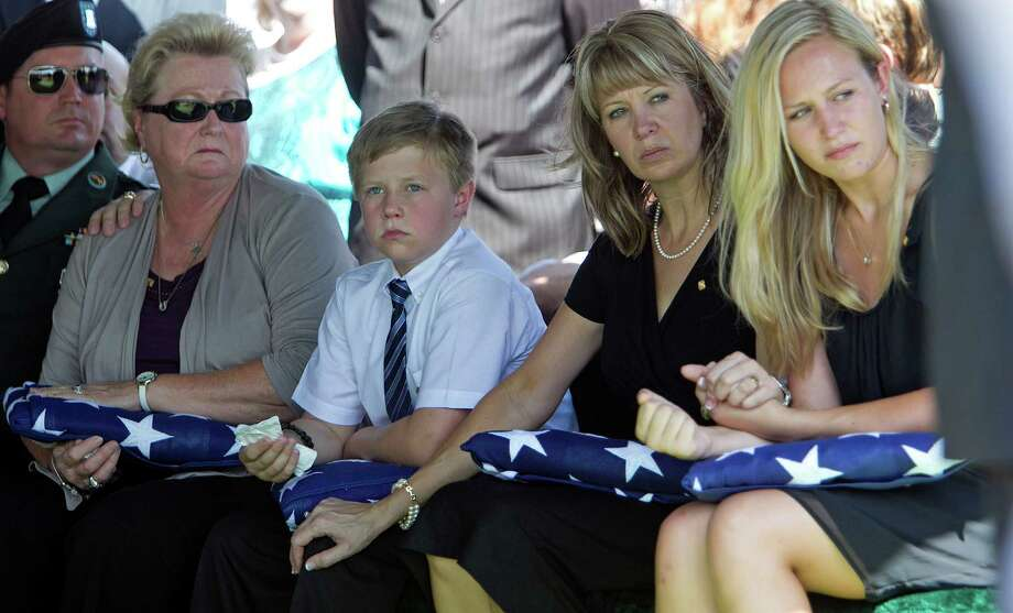 Lt Col. Roy Tisdale's brother Sgt. First Class Charles Tisdale left, his mother Linda Tisdale, Lt. Col Tisdale's son Lane Tisdale, wife Kim Tisdale and daughter Megan Tisdale right, during the burial ceremony for Lt. Col. Tisdale at the Aggie Field of Honor at the City of College Station Memorial Cemetery Thursday, July 5, 2012, in College Station. Lt. Col. Tisdale was shot to death at Fort Bragg by another soldier. Photo: James Nielsen / © Houston Chronicle 2012